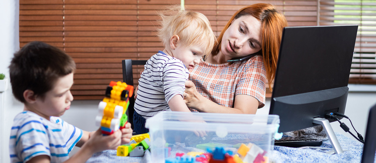 woman talking on the phone and holding young kids while trying to work remotely