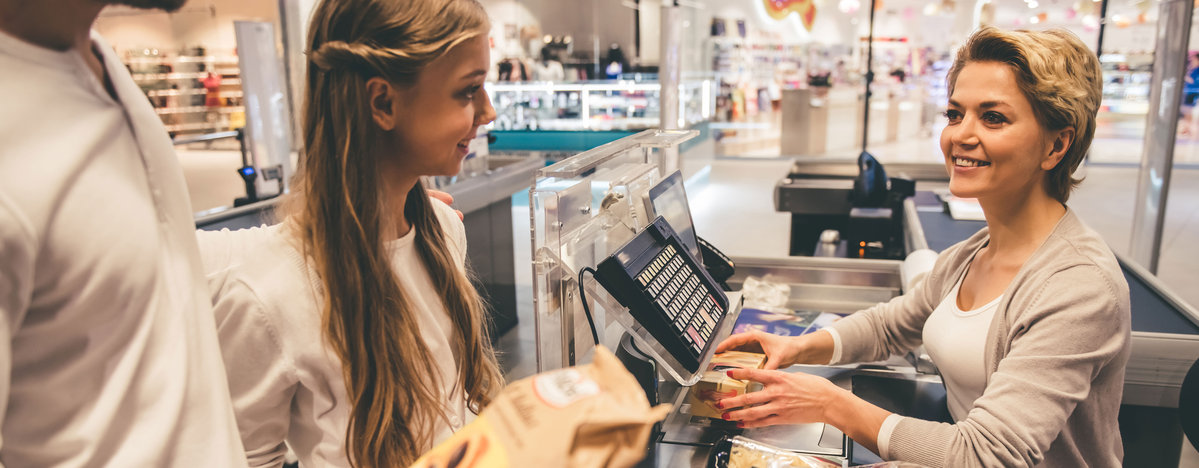 smiling cashier servicing a young couple