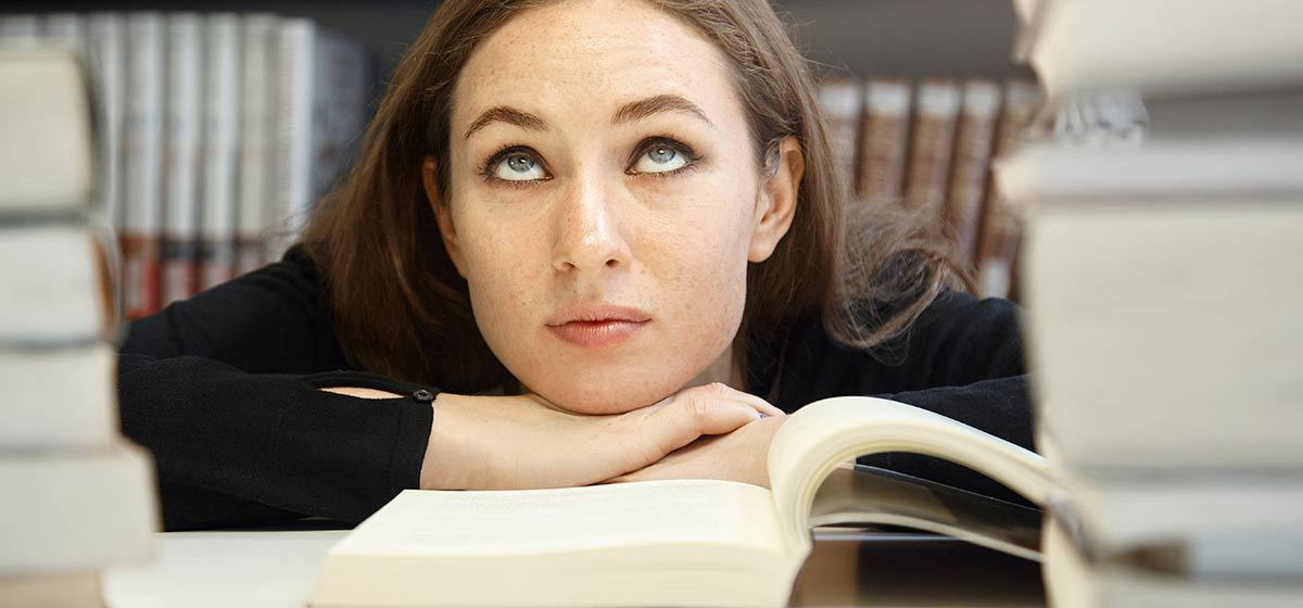 a woman rolling her eyes while being bored in a library surrounded by books