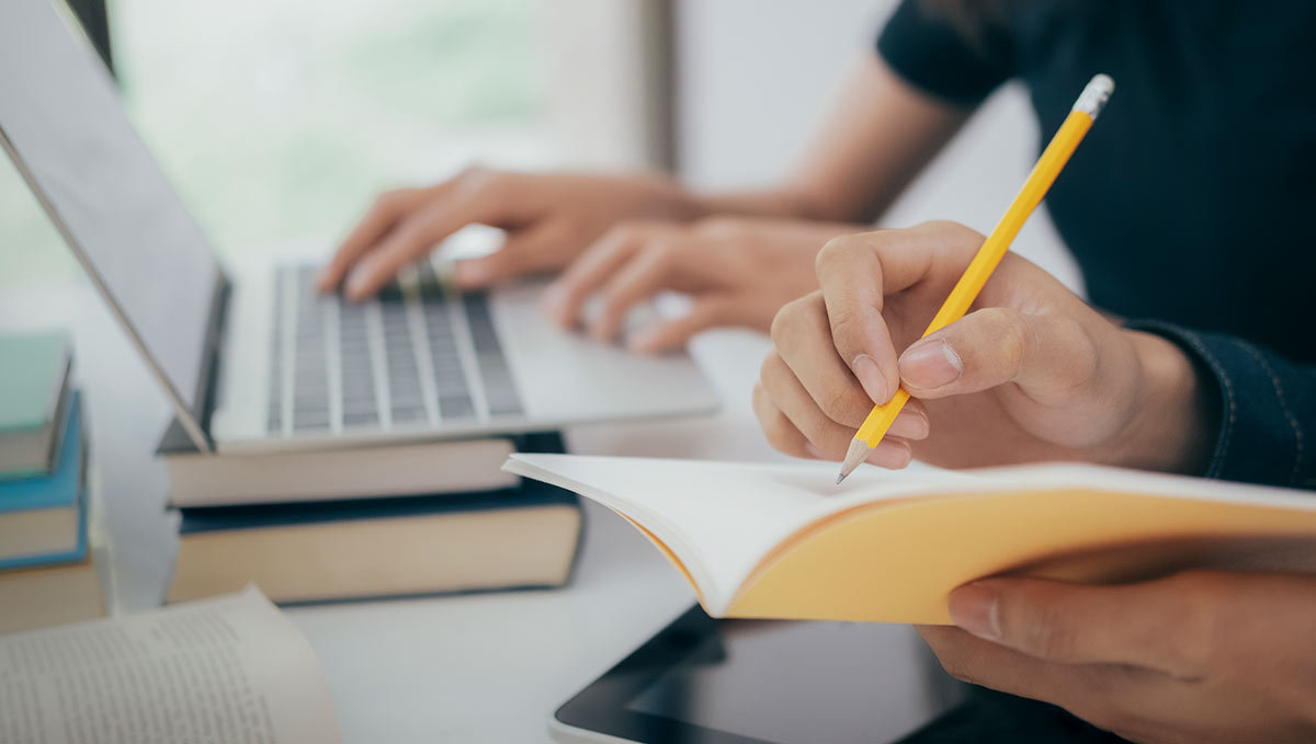 a person writing in an orange notebook and another person behind them typing on a laptop