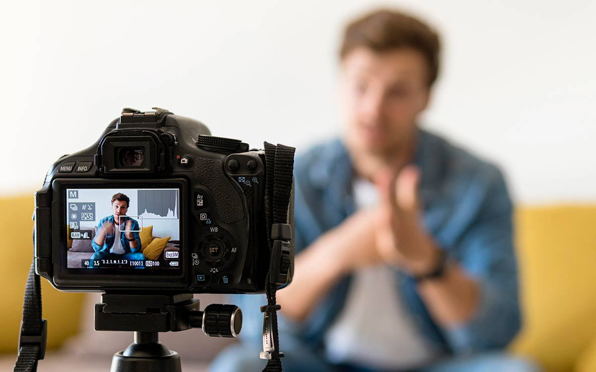 a man sitting in front of a camera making an explainer video for article on video lead generation