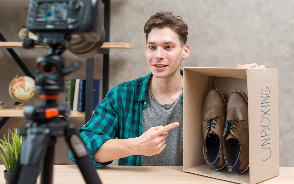 man unboxing and reviewing shoes for article on video lead generation