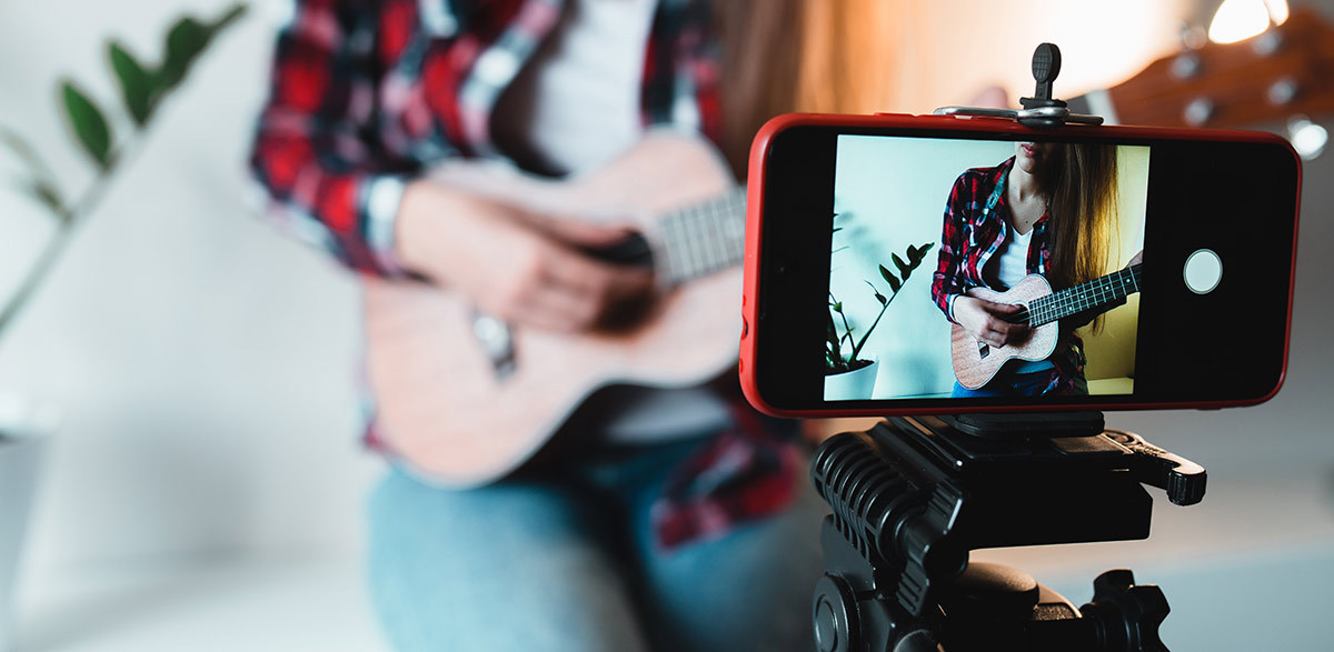 a girl playing guitar on camera