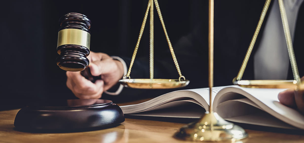 a judge with a hammer and scales in front of him