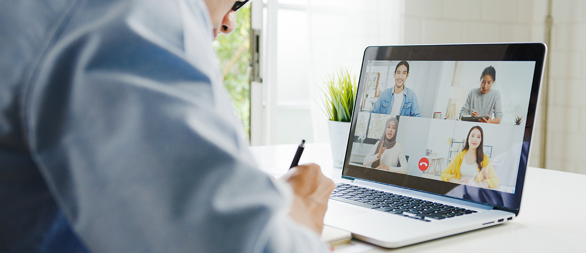 man sitting in front of a laptop in a group skype video call while working remotely