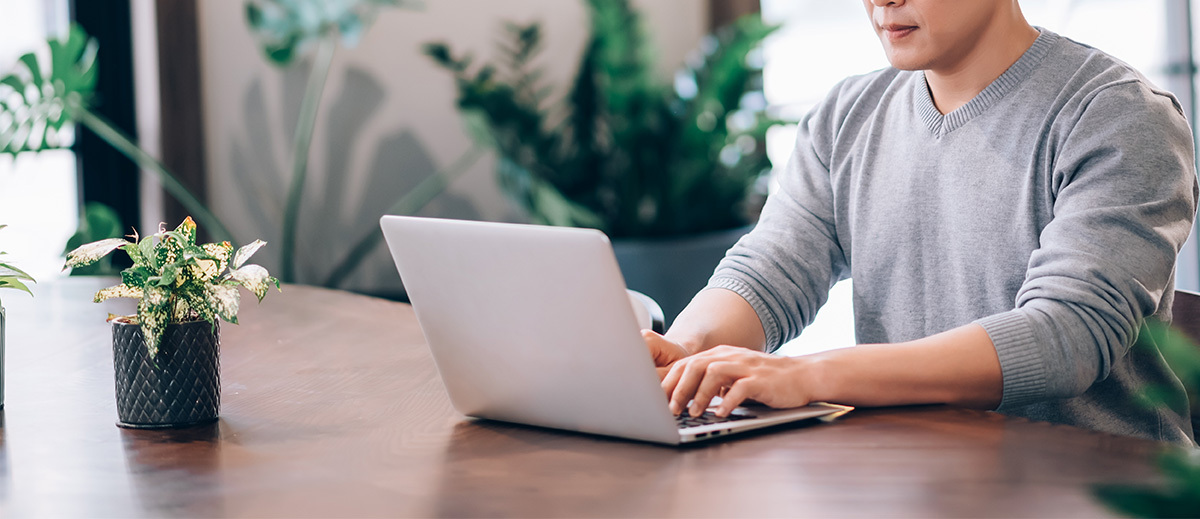 man sitting at a laptop working remotely