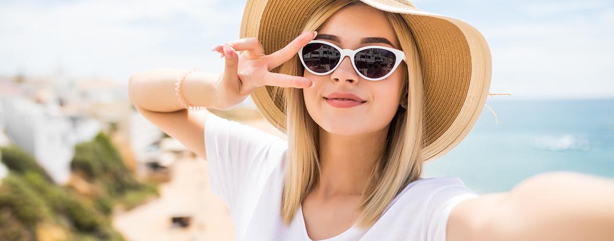 woman in a straw hat taking a selfie