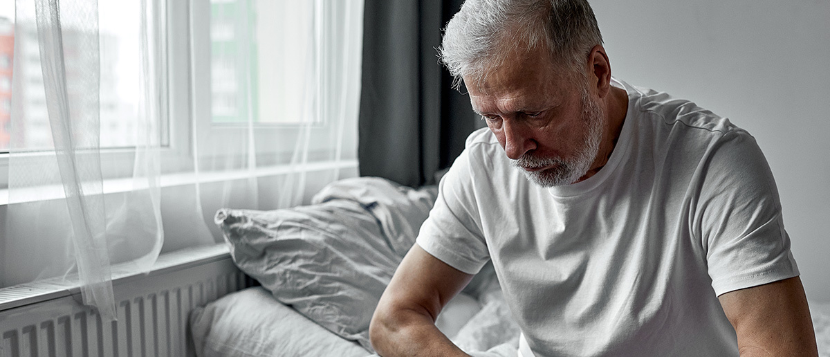 a tired old man sitting on a bed